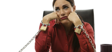 businesswoman chained to her office desk at work