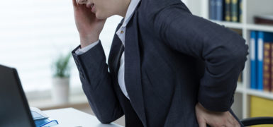 Women with problem with spine at office work
