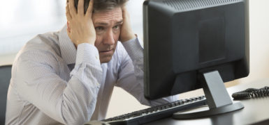 Exhausted mature businessman leaning while looking at computer monitor in office